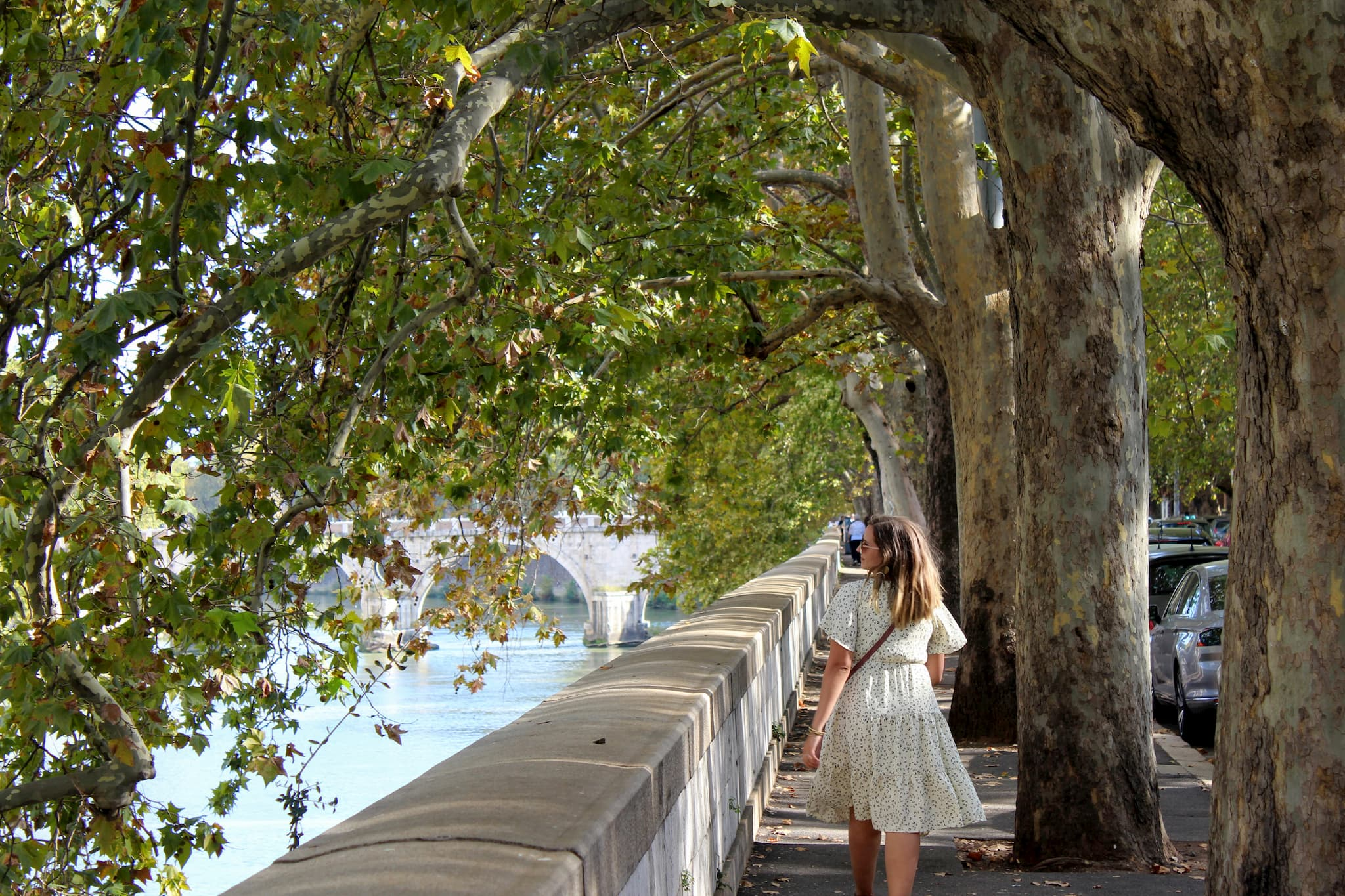 Woman walking down a sidewalk with tree branches stretching overhead towards the river down below