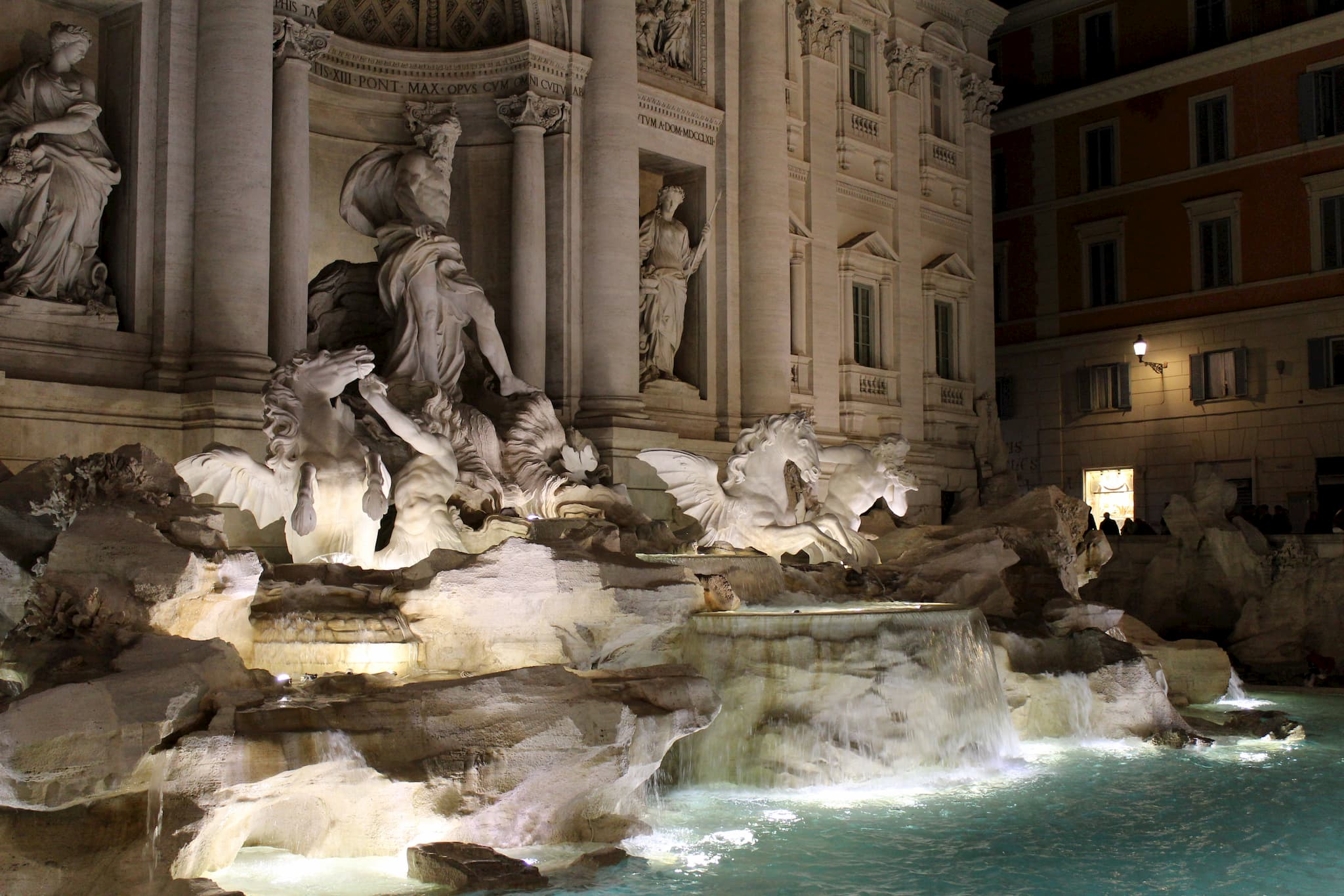 Marble carved statues forming a fountain behind a pool of water lit up in the nighttime