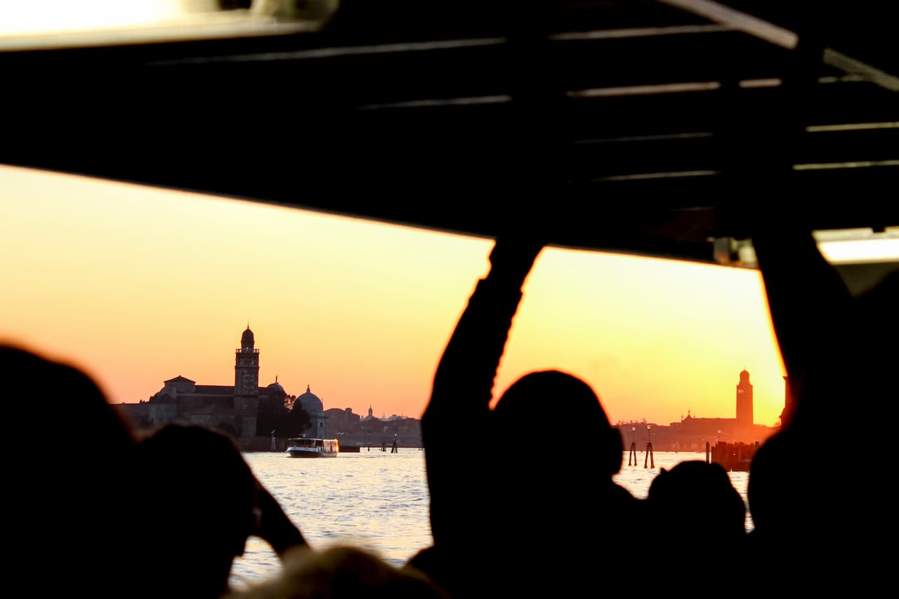 Silhouette of people inside a boat looking out at a city at sunset.