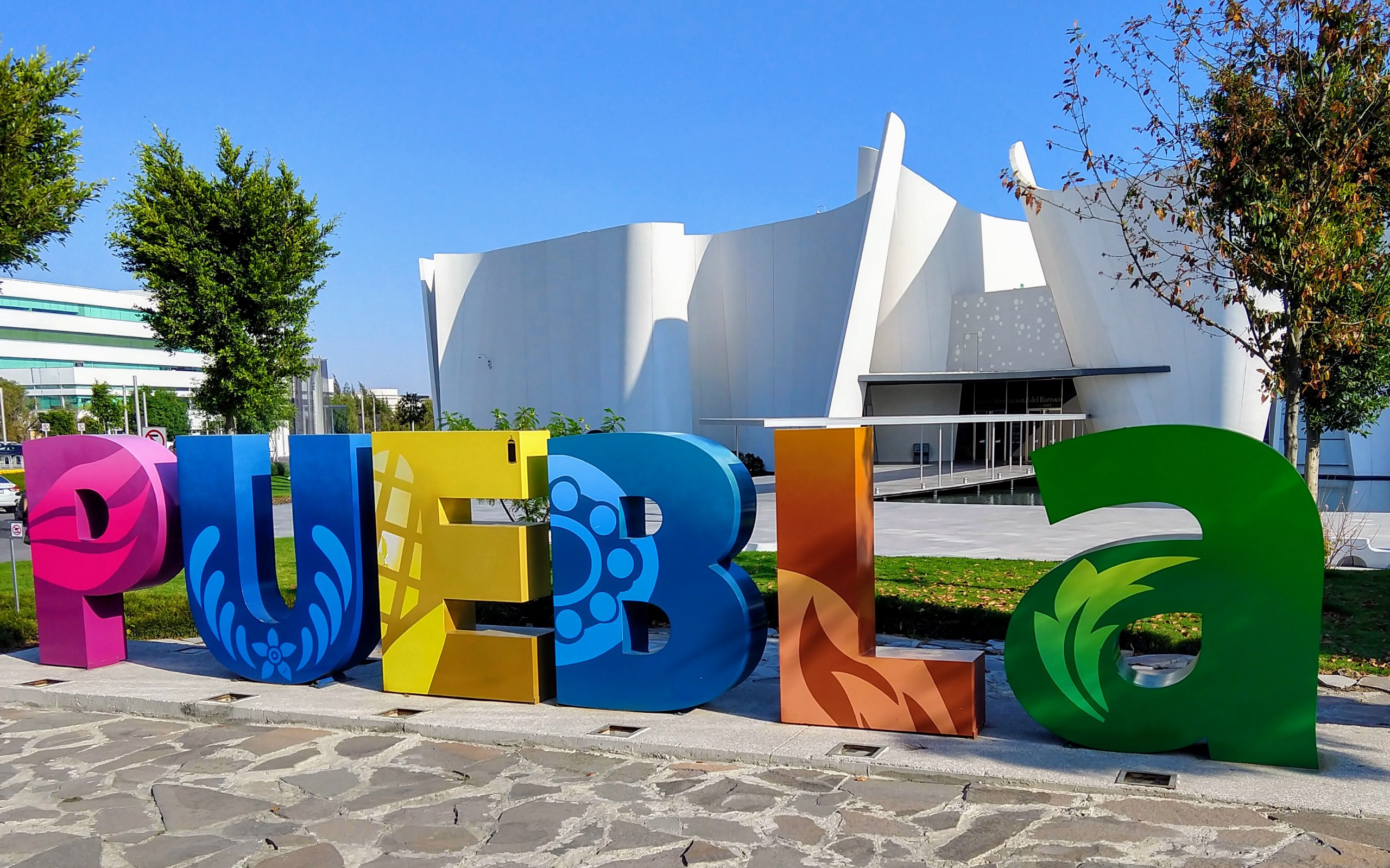 Colorful letters mounted to the ground spelling puebla with a white museum in the background with tall, white, curving walls