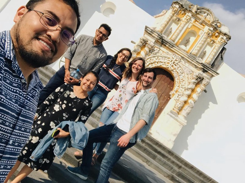6 young people, 4 mexican, 2 white taking a selfie in front of a white building with a decorated entryway
