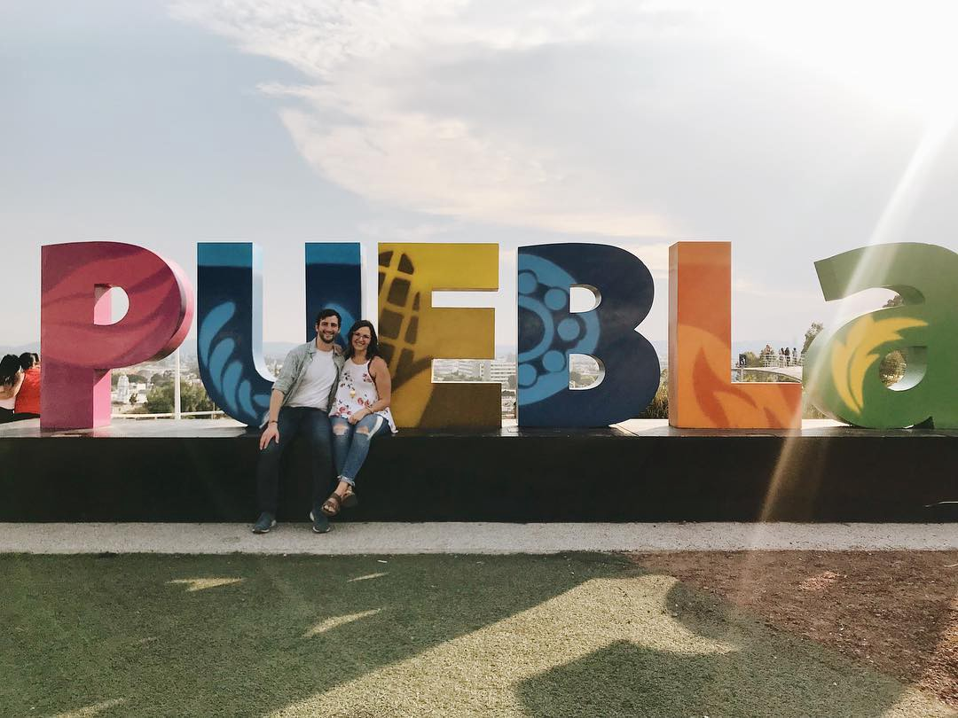 Colorful letters mounted to the ground spelling puebla with a couple sitting on the base